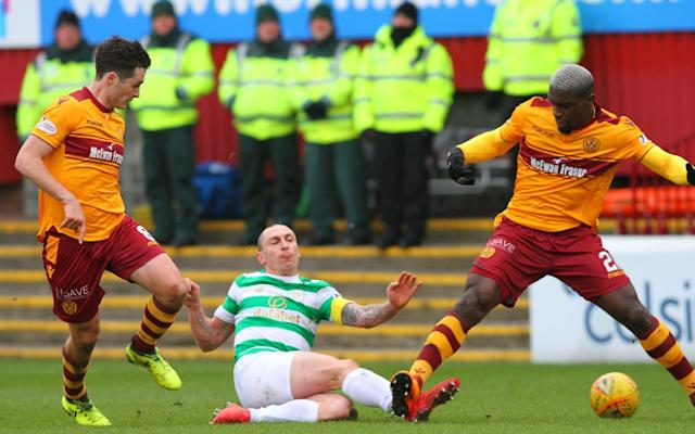 "An absorbing contest at Fir Park saw Celtic increase their lead over Rangers to 10 points as, for the second week in succession, they were involved in a game which finished short of the full complement of players. In contrast to their previous outing at Ibrox, where Jozo Simunovic was sent off but Celtic won, on this occasion Motherwell were depleted by the dismissal of Cedric Kipre but kept a clean sheet against the league leaders in a game notable for fine performances by both goalkeepers. The Celtic team selection contained bad news for Alex McLeish ahead of Scotland's friendly against Costa Rica at Hampden Park on Friday. Absent was Kieran Tierney, victim of what Celtic manager Brendan Rodgers described as a tweaked calf. Motherwell, too, were minus significant players in Craig Tanner and Andy Rose, both having sustained knee injuries. The evidence of the opening 10 minutes suggested that Motherwell were more afflicted than the visitors by their casualties and the possession ratio favoured the champions by 3:1, but Chris Cadden signalled a shift in the balance of opportunities when he struck a speculative effort from 25 yards that was blocked by Scott Bain. The Celtic goalkeeper had been third choice behind Craig Gordon and Dorus de Vries, but injuries to both meant that he made his club debut at Ibrox and was sufficiently impressive to retain his place at the expense of his Dutch colleague, who was on the bench. Bain was forced to be surprisingly active throughout the rest of the first half but he should have been beaten when Curtis Main met a cross from Elliot Frear with a downward header from close range. The English striker, however, did not get sufficient force to put the ball beyond the keeper, who dropped to his left to scoop it off the line. A third attempt to confound Bain within two minutes was similarly frustrated. Frear again provided the prompt with another high ball from the left flank, this time played off Main's chest to Ryan Bowman, whose shot on the bounce was almost straight at the goalkeeper, who was able to make another crucial intervention. Motherwell continued to animate their fans with expansive play and had supporters on their feet for what looked a certain goal from a fiery, low free kick from 30 yards by Main, but Bain dived full length to turn the ball around the post. His next test was to read a dangerous chip from Cadden, which was duly tipped over the crossbar. Motherwell's momentum was checked four minutes before the break by a needless reaction by Kipre, who stuck out a boot when shoved by Brown. The action was petulant rather than malicious but it took place in full view of Craig Thomson, who immediately showed the red card to the French midfielder. It was the fifth time this season that Thomson had sent off a Motherwell player. Kipre took his time departing the scene, protesting all the while that he had done nothing to merit the sanction. In that regard, he had the support of Stephen Robinson. ""I'm 100% certain it's not a red card,"" the Motherwell manager said. ""Cedric has brushed his leg against him, certainly not the stamp that was indicated. ""It could have been two yellow cards for the boys and nobody would have blinked an eye. It spoiled the game for the supporters again. We've got a big crowd, the game is very competitive and then we have to sit back and play for a point."" The balance of play pivoted upon the dismissal and beyond the interval it was Trevor Carson who had to produce a sequence of saves to keep Celtic at bay. After defying James Forrest, the Northern Irishman thwarted Tom Rogic twice within a minute with eye-catching blocks. Celtic tried to spring the home defence by ceaselessly working the ball from flank to flank and fuelled their efforts by sending on Stuart Armstrong, Scott Sinclair and Patrick Roberts for Olivier Ntcham, James Forrest and Odsonne Edouard. Motherwell, though, defended doggedly, never more so than in the last few seconds of stoppage time. They had mustered sufficient stamina to mount a late surge on the Celtic box where Main tried to hustle Jack Hendry, who retaliated by grabbing the striker's jersey. Main and the Motherwell fans howled for a penalty kick but Celtic broke to the other end where Sinclair, with a clear view of goal, got his shot away only for the tireless Richard Tait to throw out one leg for a spectacular block – sufficient to maintain the Steelmen's frail hopes of a top-six finish and also to guarantee the same prize for Kilmarnock."