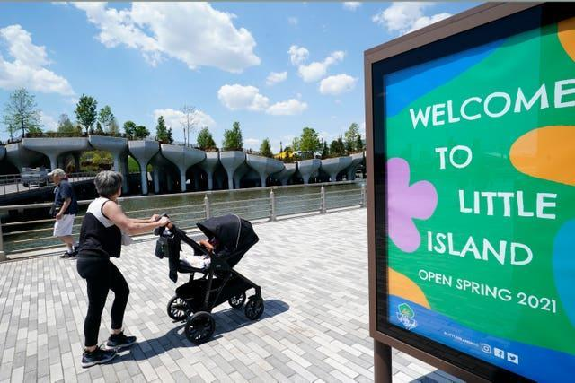 A woman rolls a baby carriage past a series of concrete tulip pots that support Little Island in New York