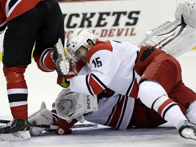 Carolina Hurricanes left wing Tuomo Ruutu (15), of Finland, collides with teammate goalie Cam Ward, bottom, while trying to avoid the skate of New Jersey Devils left wing Patrik Elias, left, of the Czech Republic, while defending on a play during the second period of an NHL hockey game on Wednesday, Nov. 27, 2013, in Newark, N.J. (AP Photo/Julio Cortez)