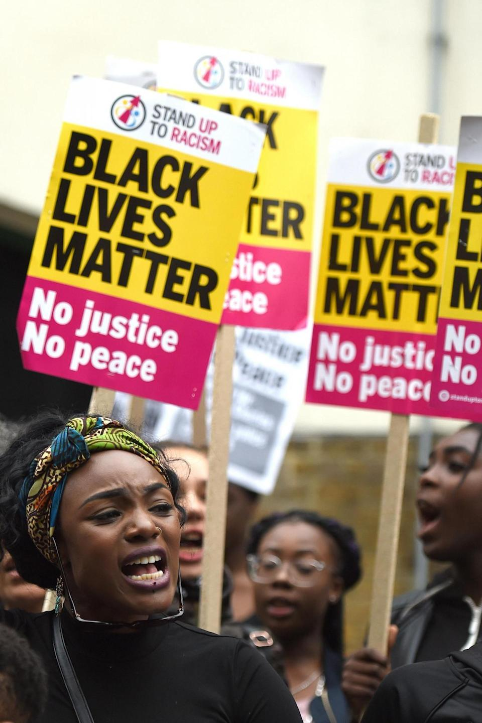Members from Hackney Stand Up To Racism protest outside Stoke Newington Police Station. (PA)