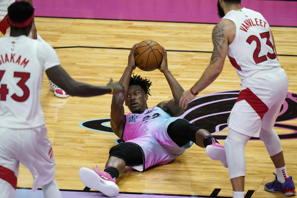 Miami Heat forward Jimmy Butler (22) looks to pass in between Toronto Raptors forward Pascal Siakam (43) and guard Fred VanVleet (23) during the second half of an NBA basketball game, Wednesday, Feb. 24, 2021, in Miami. (AP Photo/Lynne Sladky)