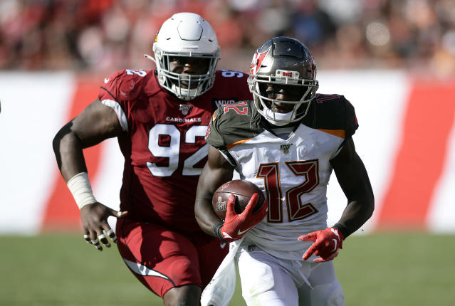 Tampa Bay Buccaneers wide receiver Chris Godwin (12) outruns Arizona Cardinals defensive end Zach Kerr (92) after a catach during the second half of an NFL football game Sunday, Nov. 10, 2019, in Tampa, Fla. (AP Photo/Jason Behnken)