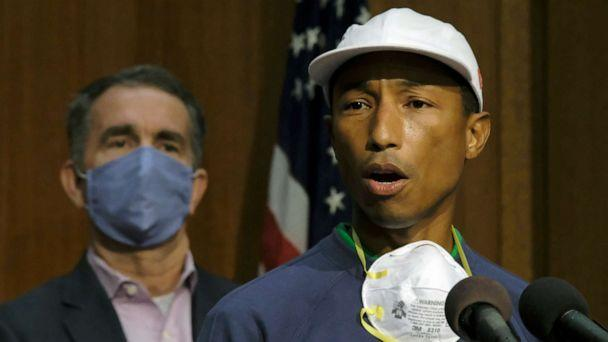 PHOTO: Performing artist and Virginia native Pharrell Williams, right, speaks about the plan to make Juneteenth a state holiday as Virginia Gov. Ralph Northam, left, listens during a press briefing in Richmond, Va., Tuesday, June 16, 2020. (Bob Brown/Richmond Times-Dispatch via AP)