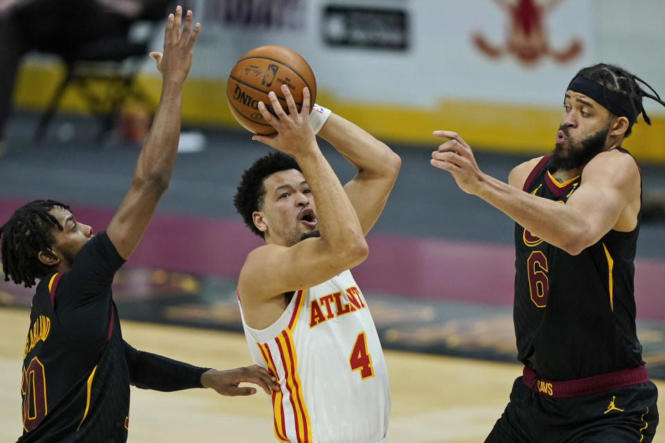 Atlanta Hawks' Skylar Mays (4) drives to the basket between Cleveland Cavaliers' Darius Garland (10) and JaVale McGee (6) in the second half of an NBA basketball game, Tuesday, Feb. 23, 2021, in Cleveland. (AP Photo/Tony Dejak)