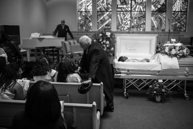<p>Spencer Leak Sr consoles a family at a funeral he helped organize at the New Life Center Church COGIC on Chicago's South Side. (Photo: Jon Lowenstein/NOOR for Yahoo News) </p>