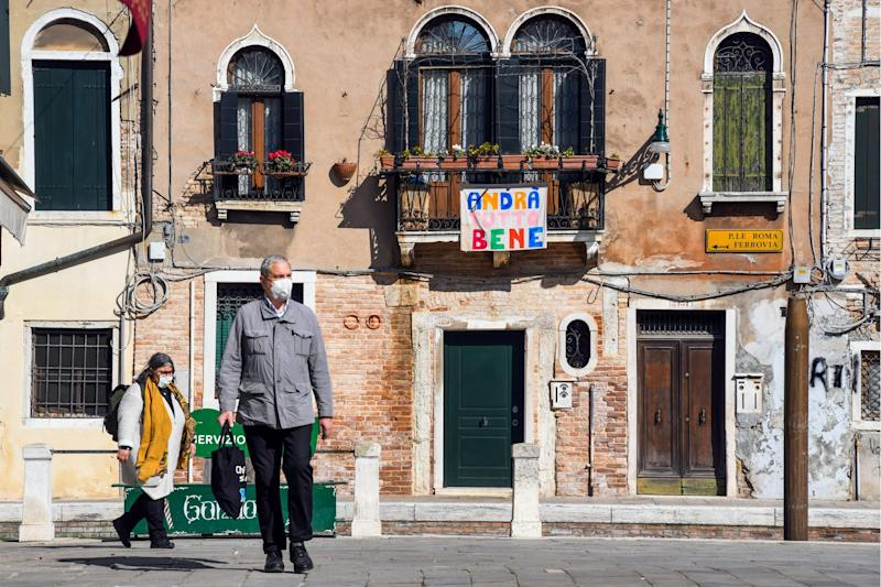 People wearing a face mask go out past a sign reading 'Everything will be alright' in Venice during the country's lockdown within the new coronavirus crisis: ANDREA PATTARO/AFP via Getty Images