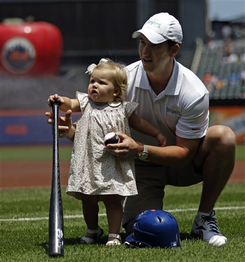 New York Giants quarterback Eli Manning holds daughter Ava at a baseball game between the New York Mets and the Cincinnati Reds baseball game at Citi Field in New York, Sunday, June 17, 2012. (AP Photo/Kathy Willens)