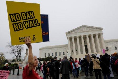 A protester holds a placard outside the U.S. Supreme Court, while the court justices consider case regarding presidential powers as it weighs the legality of President Donald Trump's latest travel ban targeting people from Muslim-majority countries, in Washington, DC, U.S., April 25, 2018. REUTERS/Yuri Gripas
