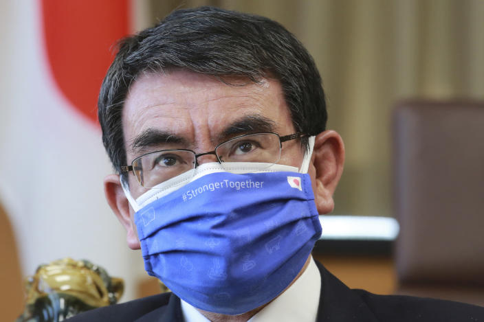 FILE - In this March 29, 2021, file photo, Japanese Vaccine Minister Taro Kono wearing a face mask with Japanese and EU flags on it speaks during an interview in Tokyo. Kono said on Thursday, April 15, 2021, even if the Olympics go on, there may be no fans of any kind in the venues. He said it's probably Olympics will have to held in empty venues, particularly as cases surge across the country. (AP Photo/Koji Sasahara, File)