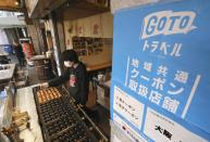 """A vendor makes takoyaki, small dumpling with fried octopus in it beside a poster for """"GoTo Travel"""" campaign in Osaka, western Japan Monday, Dec. 28, 2020. The government's """"GoTo Travel"""" and """"GoTo Eat"""" campaigns, provide big discounts for domestic travel and dining out. The programs were launched in the summer, before Prime Minister Yoshihide Suga took office. The suspension took effect Monday after Suga announced plans to do so earlier this month, but many Japanese see them as a factor in encouraging the spread of the virus and believe they should have been halted sooner. (Takumi Sato/Kyodo News via AP)"""