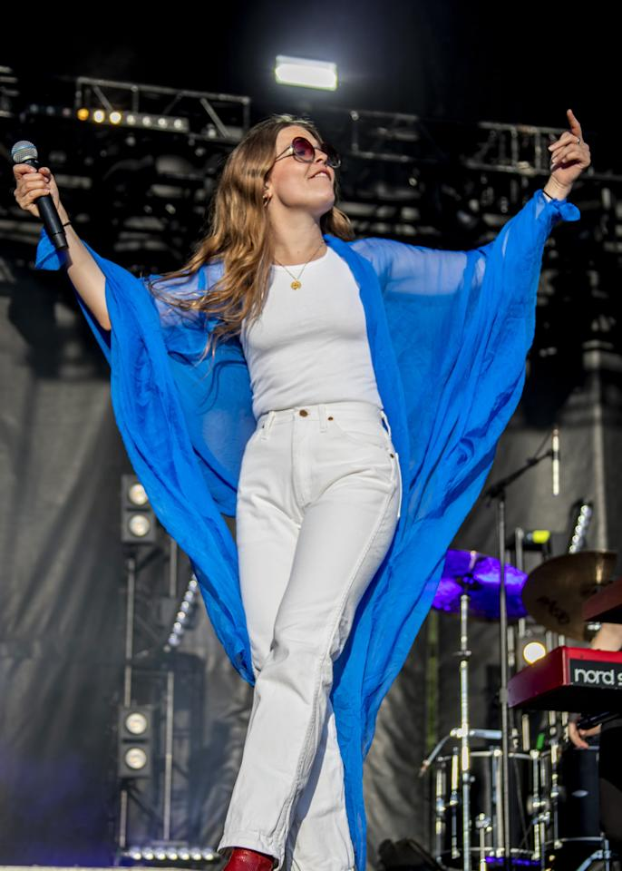 <p>Showing her love for white denim, she wore this straight-leg, high-wasited pair with a white tank, red booties, a blue shawl, and round shades. </p>