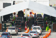 Vehicles line up as a healthcare workers help people check in as they are being tested at the COVID-19 drive-thru testing center at Hard Rock Stadium in Miami Gardens, Fla. on Wednesday, Oct. 28, 2020. (David Santiago/Miami Herald via AP)