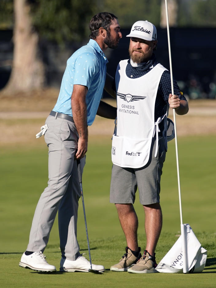Max Homa, left, hugs his caddie on the 14th green after defeating Tony Finau in a two-hole playoff to win the Genesis Invitational golf tournament at Riviera Country Club, Sunday, Feb. 21, 2021, in the Pacific Palisades area of Los Angeles. (AP Photo/Ryan Kang)