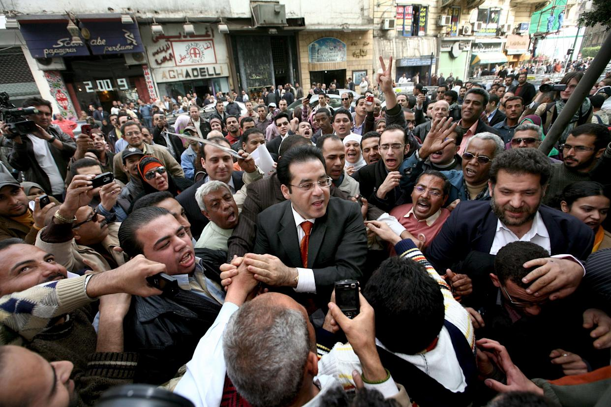 Ayman Nour (c) the Leader of the Ghad Opposition Party is mobbed by supporters outside his party's headquarters following his release from prison on February 19, 2009. (Mike Nelson/EPA/Shutterstock)