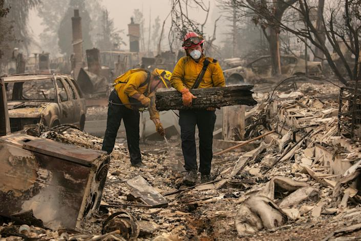 Jackson County District 5 firefighter Captain Aaron Bustard, right, and Andy Buckingham work on a smouldering fire in a burned neighbourhood as destructive wildfires devastate the region on Friday (AP)