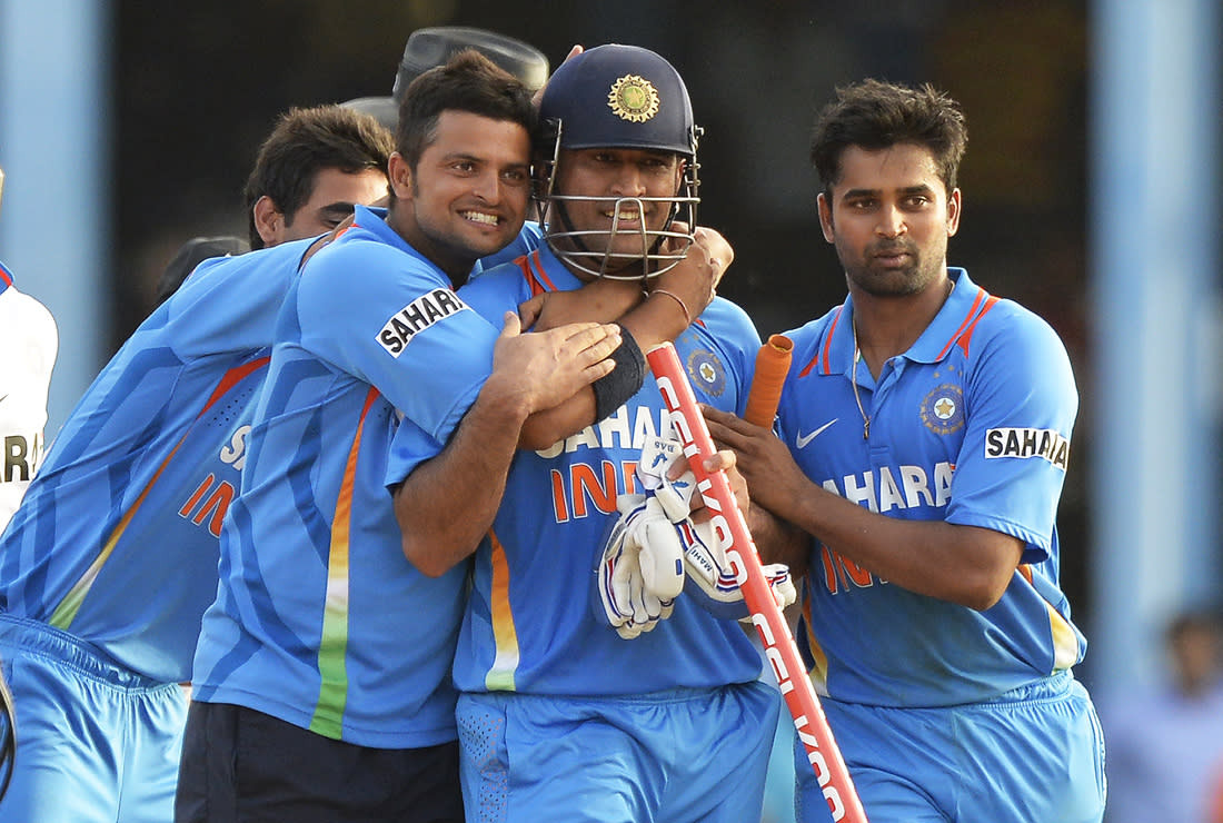 Indian cricketers celebrate with their team captain Mahendra Sing Dhoni (C) following their victory during the final match of the Tri-Nation series between India and Sri Lanka at the Queen's Park Oval stadium in Port of Spain on July 11, 2013. India defeated Sri Lanka by 1 wicket to win the series. AFP PHOTO/Jewel Samad