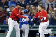 Boston Red Sox's Christian Vazquez, right, celebrates with third base coach Carlos Febles after hitting a walkoff home run as Toronto Blue Jays' Jordan Romano (68) enters the dugout during the 10th inning of a baseball game in Boston, Friday, June 21, 2019. (AP Photo/Michael Dwyer)