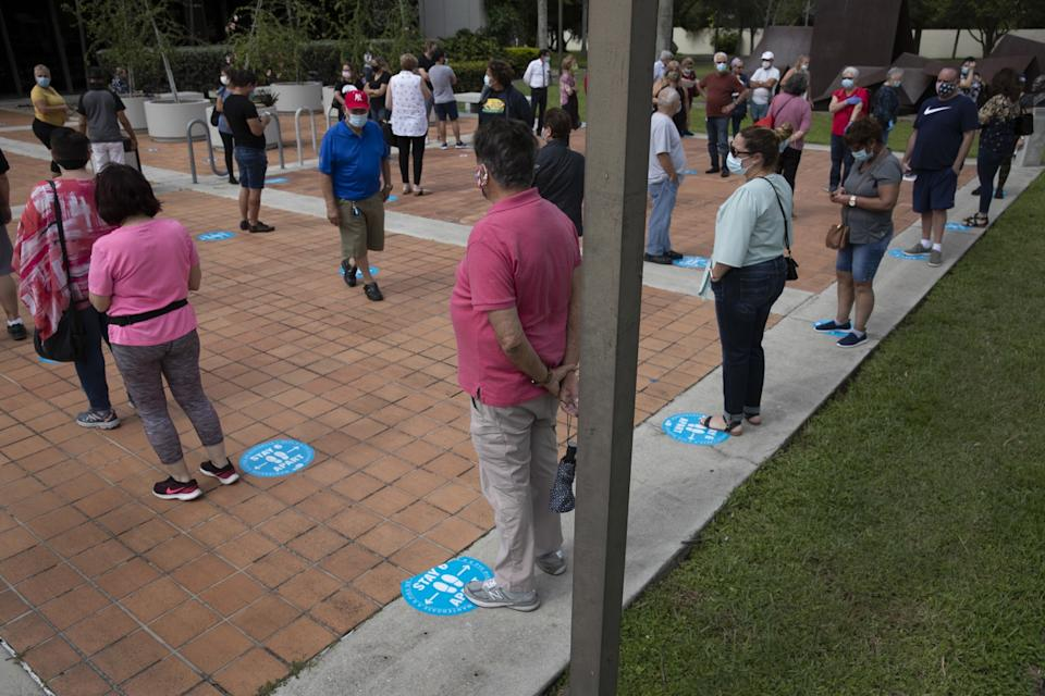 Early voters wait to cast their ballots Monday at a library in Westchester, Fla.