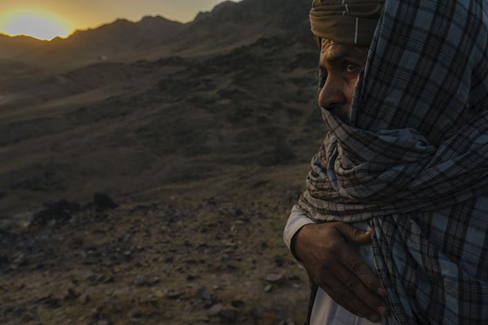 A Taliban commander looks over mountains.