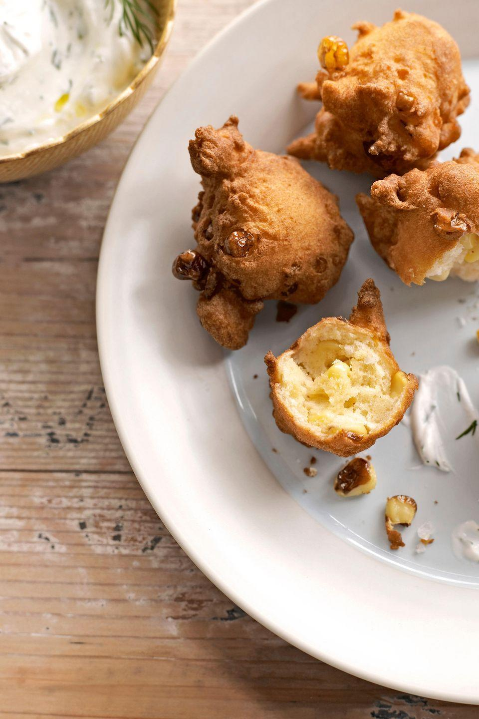 """<p>Made with everyday pantry staples and kernels cut straight from the cob, these airy fritters will get eaten up as fast as you can fry them. </p><p><strong><a href=""""https://www.countryliving.com/food-drinks/recipes/a2911/corn-fritters-recipe/"""" rel=""""nofollow noopener"""" target=""""_blank"""" data-ylk=""""slk:Get the recipe"""" class=""""link rapid-noclick-resp"""">Get the recipe</a>.</strong></p>"""
