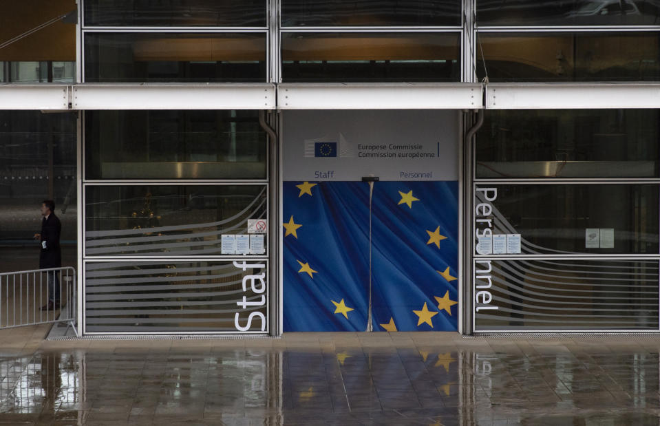 A man takes a break outside of EU headquarters in Brussels, Wednesday, Dec. 23, 2020. France insisted on Wednesday that European Union negotiators should not yield to any time pressure imposed by the Jan. 1 economic cutoff date in the talks with Britain on a trade agreement in the wake of the Brexit divorce, arguing no deal would be better than a bad one. (AP Photo/Virginia Mayo)