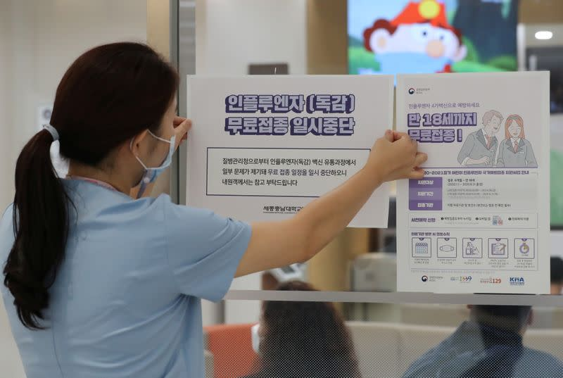 A health worker attaches a notice for suspension of influenza vaccination programs on an entrance of a hospital in Sejong