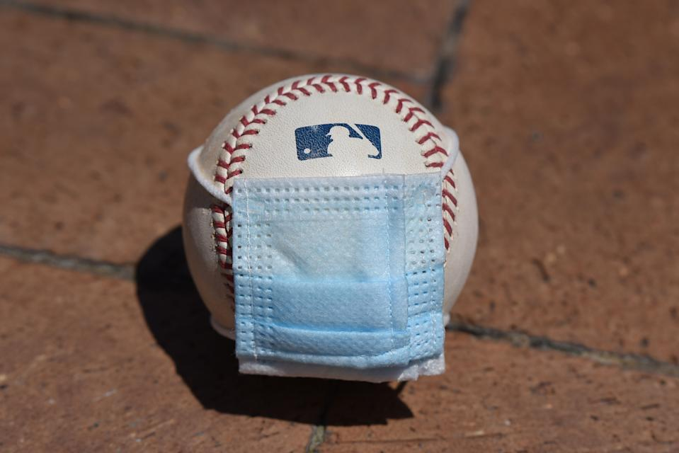 A baseball with a surgical mask placed on it.