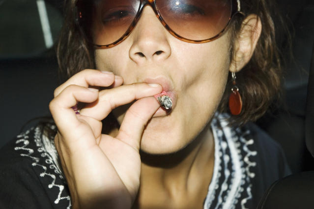Close-up of young woman in sunglasses smoking a marijuana joint. (Getty Images)
