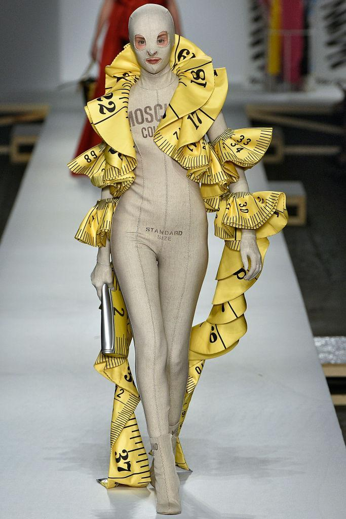 <p>A model walks the runway wearing a large tape-measure scarf at the Moschino show on Sept. 20 in Milan. (Photo: Victor Virgile/Gamma-Rapho via Getty Images) </p>