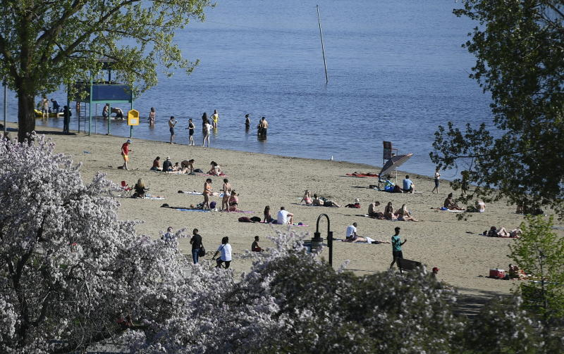 People practice physical distancing as they enjoy the warm weather at Mooney's Bay Beach in Ottawa, Ontario, Saturday, May 23, 2020, during the coronavirus pandemic. (Justin Tang/The Canadian Press via AP)