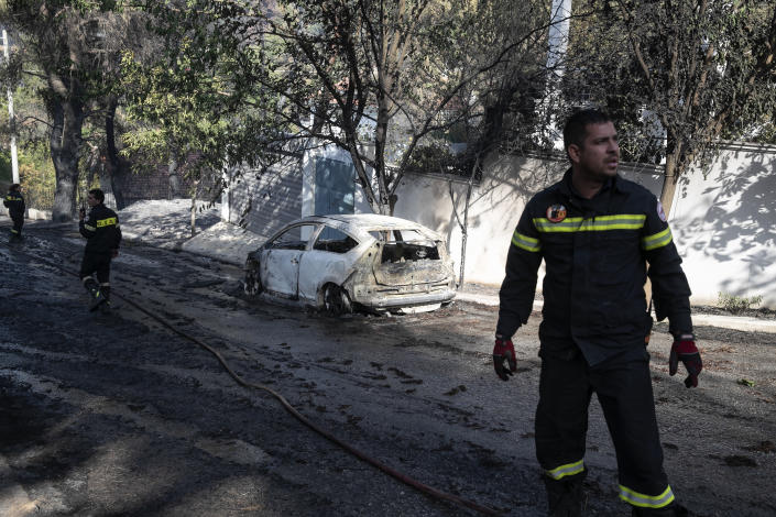 Firefighters in front of a burnt car following a forest fire at Dionysos northern suburb of Athens, on Tuesday, July 27, 2021. Greek authorities have evacuated several areas north of Athens as a wildfire swept through a hillside forest and threatened homes despite a large operation mounted by firefighters. (AP Photo/Yorgos Karahalis)