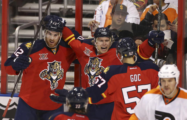 Florida Panthers players Jimmy Hayes (12), Sean Bergenheim (20) and Marcel Goc (57) celebrate Bergenheim second second period goal during the second period of the NHL hockey game in Sunrise, Fla., Monday, Nov. 25, 2013 against the Philadephia Flyers. (AP Photo/J Pat Carter)