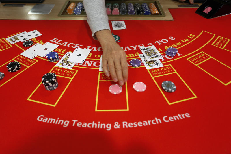 In this Nov. 25, 2012 photo, a gambling school student practices on a table in Macau, China. The students sitting around the roulette table are getting schooled on how to quickly calculate payoffs for the casino game by glancing at how the bets are placed. Elsewhere in the room, the biggest mock casino in Asia, other students are playing practice hands of blackjack or learning how to run a craps table. (AP Photo/Vincent Yu)