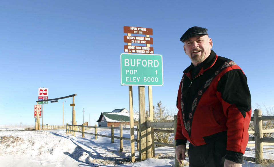 FILE - This Jan. 1, 2011 file photo shows Buford resident Don Sammons standing in front of the population sign in Buford, Wyo. The town advertised as the smallest in the United States has sold at auction for $900,000. (AP Photo/Wyoming Tribune Eagle, Michael Smith)