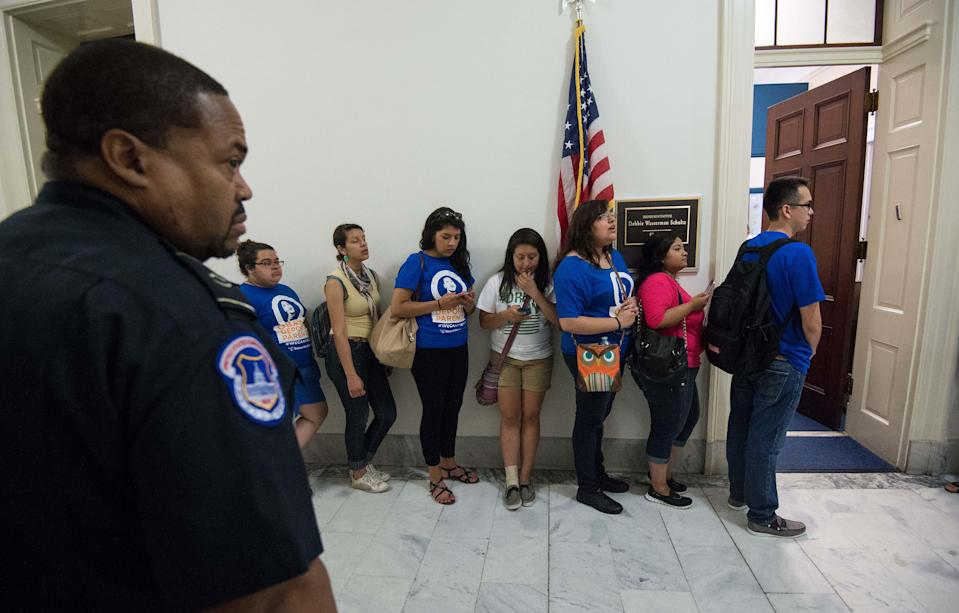 A police officer watches members of United We Dream outside the office of Representattive and Democratic National Committee chair Debbie Wasserman Schultz on Capitol Hill during a protest in Washington on June 27, 2014 (AFP Photo/Nicholas Kamm)