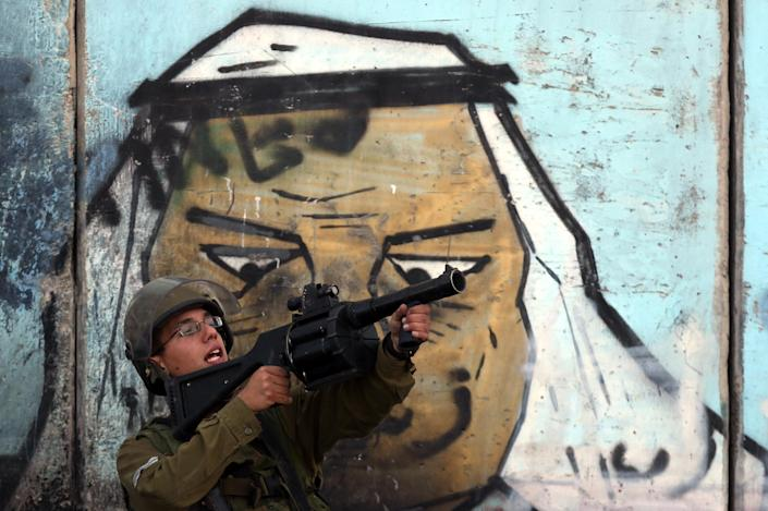 A member of the Israeli security forces aims tear gas during clashes with Palestinian protesters at the Qalandia checkpoint near the West Bank city of Ramallah, on November 2, 2014 (AFP Photo/Abbas Momani)