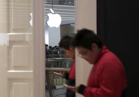 A logo of Apple Inc. is reflected on a mirror as a man looking at his mobile phone walks past near an Apple Store at Joy City department store in Tianjin