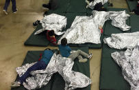 FILE - In this Sunday, June 17, 2018, file photo provided by U.S. Customs and Border Protection, people who've been taken into custody related to cases of illegal entry into the United States rest in one of the cages at a facility in McAllen, Texas. A federal volunteer at the Biden administration's largest shelter for unaccompanied immigrant children says paramedics were called regularly during her the two weeks she worked there. She said panic attacks would occur often after some of the children were taken away to be reunited with their families, dashing the hopes of those left behind. The conditions described by the volunteer highlight the stress of children who cross the U.S.-Mexico border alone and now find themselves held at unlicensed mass-scale facilities waiting to reunite with relatives. (U.S. Customs and Border Protection's Rio Grande Valley Sector via AP, File)