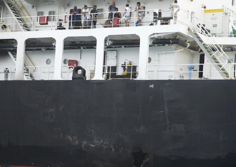 """Sailors stand on deck above a hole the U.S. Navy says was made by a limpet mine on  the damaged Panama-flagged, Japanese owned oil tanker Kokuka Courageous, anchored off Fujairah, United Arab Emirates, during a trip organized by the Navy for journalists, on Wednesday, June 19, 2019. The limpet mines used to attack the oil tanker near the Strait of Hormuz bore """"a striking resemblance"""" to similar mines displayed by Iran, a U.S. Navy explosives expert said Wednesday. Iran has denied being involved. (AP Photo/Fay Abuelgasim)"""
