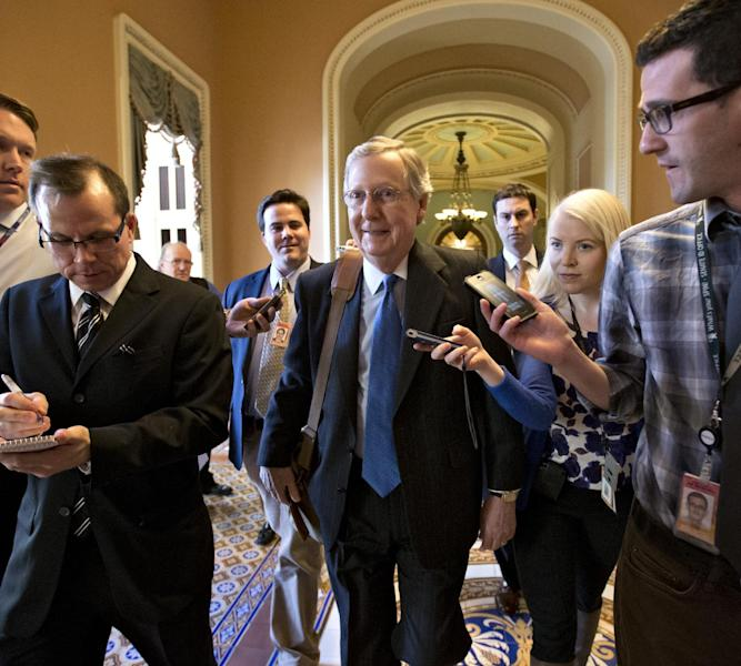 """Senate Minority Leader Mitch McConnell of Kentucky, center, arrives at his office in the Capitol as he and Senate Majority Leader Harry Reid of Neveda, try to negotiate a legislative solution to avoid the so-called """"fiscal cliff"""" in Washington, Sunday, Dec. 30, 2012. (AP Photo/J. Scott Applewhite)"""