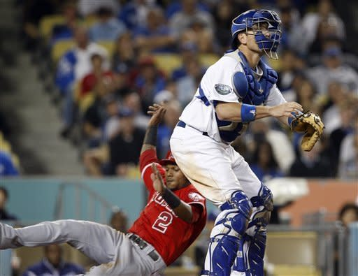 Erick Aybar of the Los Angeles Angels scores from second on a Mike Trout baase hit as Los Angeles Dodgers catcher A.J. Ellis waits for the throw in the sixth inning of an interleague baseball game at Dodger Stadium in Los Angeles Monday, June 11, 2012. (AP Photo/Reed Saxon)