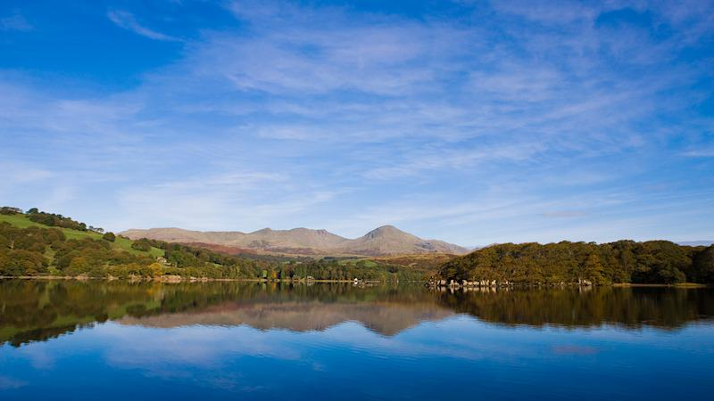 The Old Man of Coniston mountain reflected in Coniston Water