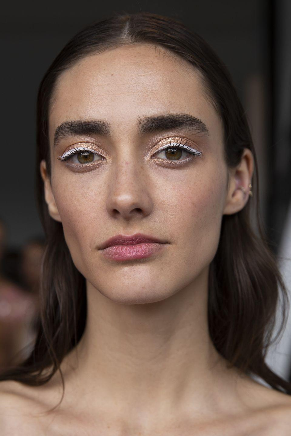 <p>Give romantic metallic eyeshadow a graphic update with white liquid eyeliner.</p>