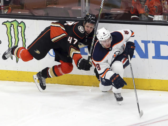 Anaheim Ducks defenseman Hampus Lindholm (47) and Edmonton Oilers right winger Ty Rattie (8) tangle in the second period of an NHL hockey game in Anaheim, Calif., Sunday, Feb. 25, 2018. (AP Photo/Reed Saxon)