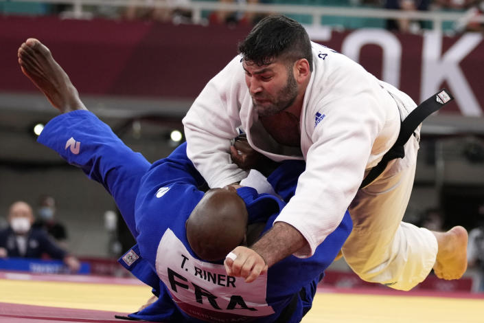 Or Sasson of Israel, top, and Teddy Riner of France compete during their men's +100kg elimination round judo match at the 2020 Summer Olympics, Friday, July 30, 2021, in Tokyo, Japan. (AP Photo/Vincent Thian)