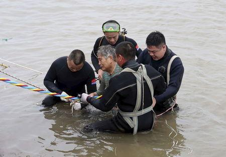 A woman is helped after being pulled out by divers from a sunken ship in Jianli, Hubei province, China, June 2, 2015. REUTERS/cnsphoto
