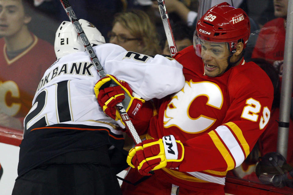 FILE - In this April 7, 2012, file photo, Anaheim Ducks' Sheldon Brookbank, left, checks Calgary Flames' Akim Aliu, a Nigerian-born Canadian, during third period NHL hockey action in Calgary, Alberta. Calgary Flames general manager Brad Treliving said the team is looking into an accusation that head coach Bill Peters directed racial slurs toward a Nigerian-born hockey player a decade ago in the minor leagues, then arranged for the players demotion when he complained. Akim Aliu tweeted Monday, Nov. 25, 2019, that Peters dropped the N bomb several times towards me in the dressing room in my rookie year because he didnt like my choice of music. (AP Photo/The Canadian Press, Jeff McIntosh, File)