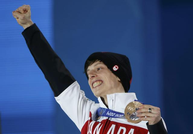 Bronze medallist Canada's Charle Cournoyer celebrates during the victory ceremony for the men's 500 metres short track speed skating event at the 2014 Sochi Winter Olympics in Sochi, February 22, 2104. REUTERS/Jim Young (RUSSIA - Tags: OLYMPICS SPORT SPEED SKATING)