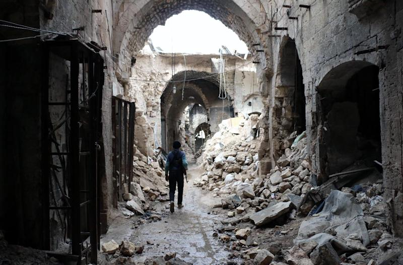 A Syrian rebel walks through a devastated alley of Aleppo's old market on February 27, 2014 (AFP Photo/Zein Al-Rifai)