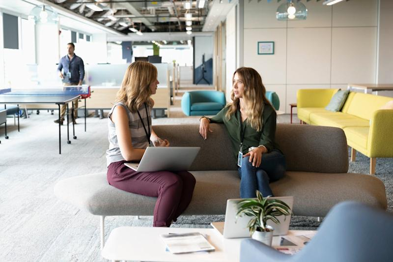 Two women in an office have a conversation on a sofa